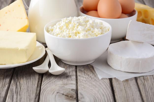 Świeże Produkty Mleczne. Mleko, Ser, Brie, Camembert, Masło, Twaróg I Jajka Na Drewnianym Stole. Premium Zdjęcia