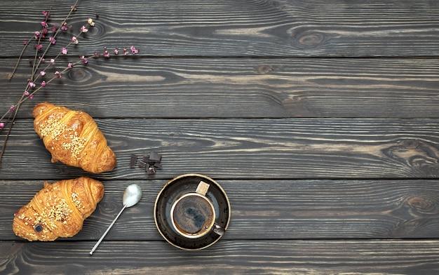 Świeże Rogaliki I Filiżanka Espresso Z Bukietem Wiosennych Kwiatów Na Stole Premium Zdjęcia