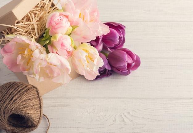 Świeże różowe tulipany, sznurek i pudełko Premium Zdjęcia