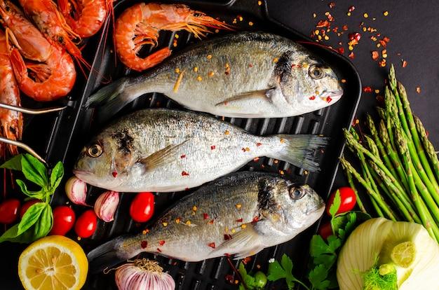 Świeże ryby dorado i krewetki tygrysie na żelaznej patelni grillowej i warzywach do gotowania Premium Zdjęcia