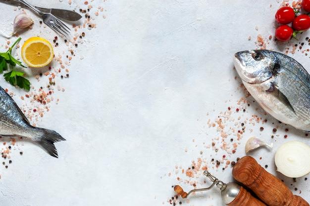 Świeże Ryby Dorado Z Przyprawami, Czosnkiem, Białą Cebulą I Przyprawami Na Białym Naczyniu Na Białym Stole Premium Zdjęcia