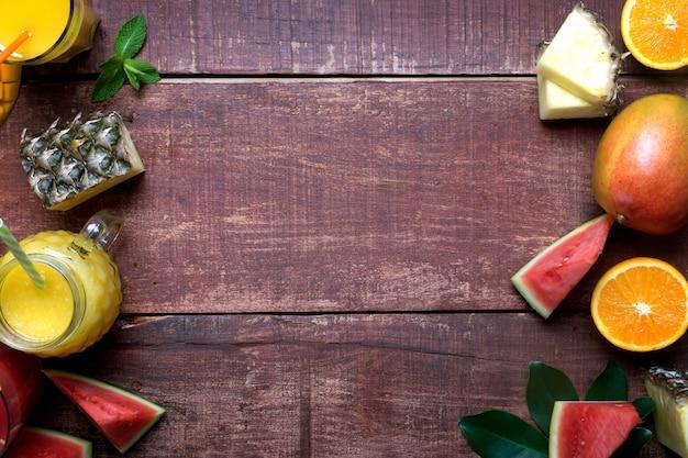 Świeże Wielo- Owoc I Smoothie Na Ciemnym Drewnianym Nieociosanym Tle, Mieszkanie Nieatutowej I Kopii Przestrzeni Premium Zdjęcia