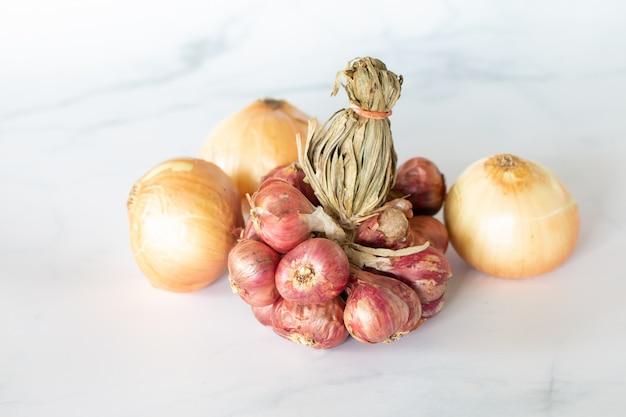 Świeże żarówki cebuli na marmurowym stole Premium Zdjęcia