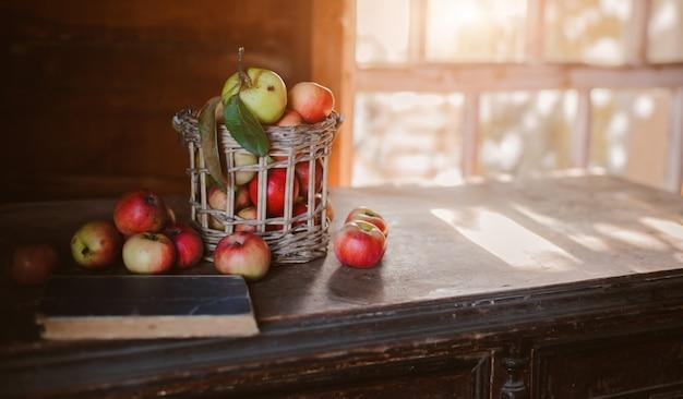 Świeże zbiory dojrzałych i zdrowych jabłek w szklanym słoju, w koszu. Premium Zdjęcia