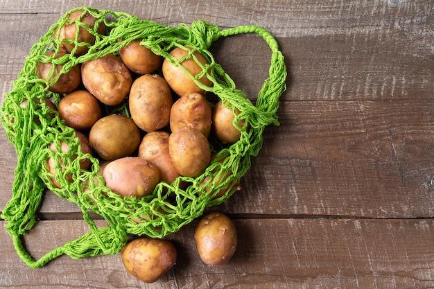 Świeże ziemniaki w eco torba na zakupy wielokrotnego użytku o zerowej siatce odpadów na białym tle, orientacja pozioma. Premium Zdjęcia