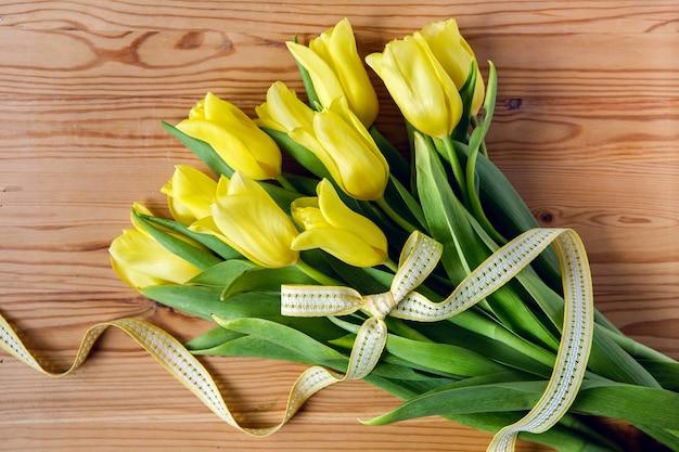 Świeże żółte Tulipany Z Jasną Wstążką Leżące Na Stole Z Drewna Premium Zdjęcia