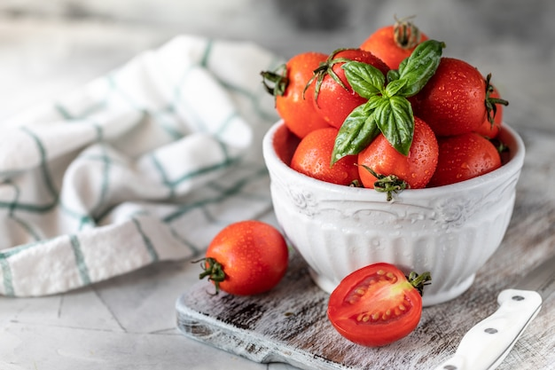 Świezi Czerwoni Czereśniowi Pomidory I Basil Opuszczają W Talerzu Na Białym Kuchennym Stole. Premium Zdjęcia