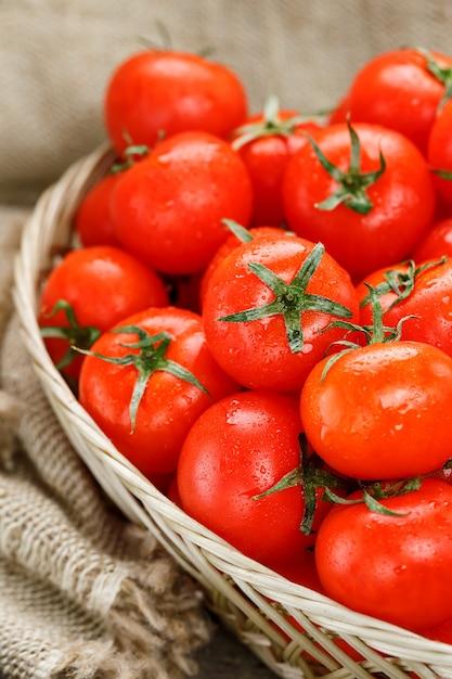 Świezi czerwoni pomidory w łozinowym koszu na starym drewnianym stole. dojrzałe i soczyste pomidory czereśniowe z kroplami wilgoci, szary drewniany stół, wokół płótna juta. w stylu rustykalnym. Premium Zdjęcia