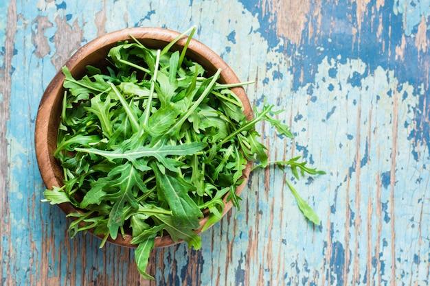 Świezi liście arugula w drewnianym pucharze na drewnianym stole. Premium Zdjęcia