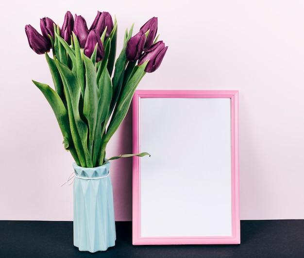 Świezi purpurowi tulipanowi kwiaty w wazie z menchiami graniczą fotografii ramę Darmowe Zdjęcia
