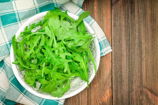 Świezi soczyści liście arugula na brown drewnianym stole. Premium Zdjęcia
