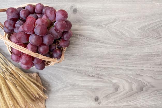 Świezi winogrona na koszykowym drewnianym tle. skopiuj miejsce na dodanie tekstu. Premium Zdjęcia