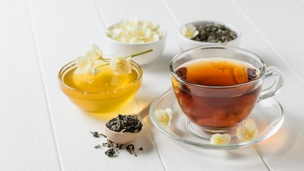 Świeżo Przygotowana Herbata Z Kwiatami Jaśminu I Miodem Na Białym Rustykalnym Stole. Premium Zdjęcia
