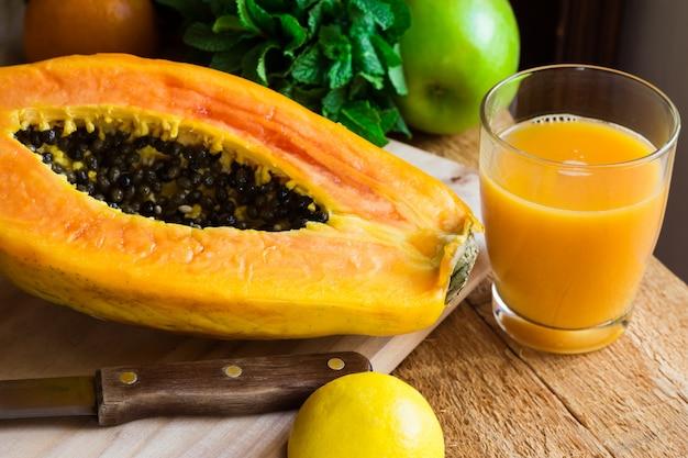 Świeżo Wciśnięty Sok Z Papai W Szkle, Dojrzałe Połówki Owoców Na Pokładzie Cięcia Drewna Premium Zdjęcia