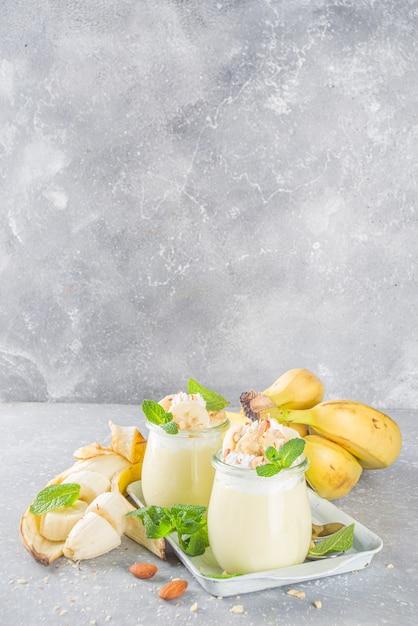 Świeży Budyń Bananowy Na śniadanie, Jogurt Bananowy. Słodki Deser W Szklankach Z Plastrami Banana I Orzechami, Surowa Wegetariańska Przekąska Premium Zdjęcia