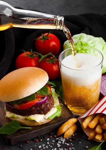 Świeży Burger Wołowy Z Sosem I Warzywami Oraz Szklanka Piwa Rzemieślniczego Z Frytkami Na Kamiennej Kuchni. Premium Zdjęcia