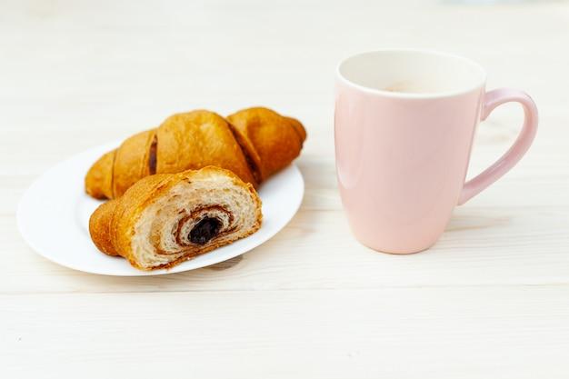 Świeży Croissant Z Czekoladą Na Białym Drewnianym Stole Premium Zdjęcia