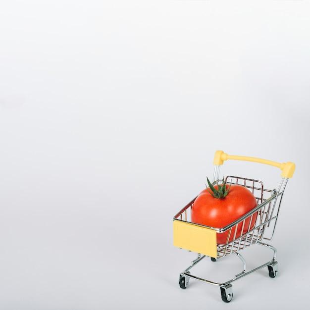 Świeży czerwony pomidor w wózek na zakupy na biel powierzchni Darmowe Zdjęcia
