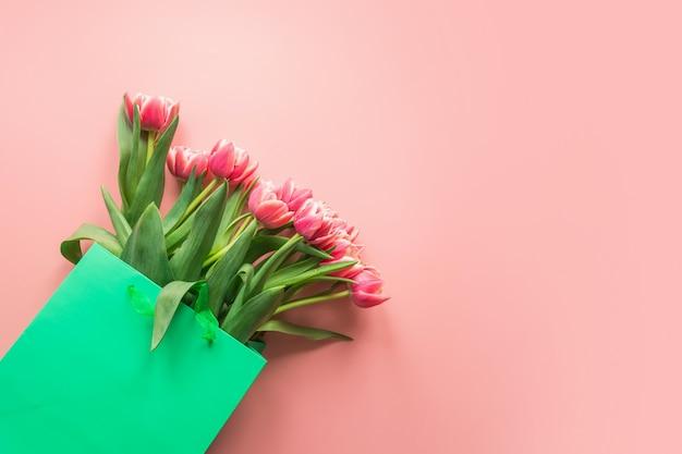Świeży Czerwony Tulipan Kwitnie W Zielonej Papierowej Torbie Na Menchiach. Wiosna. Premium Zdjęcia