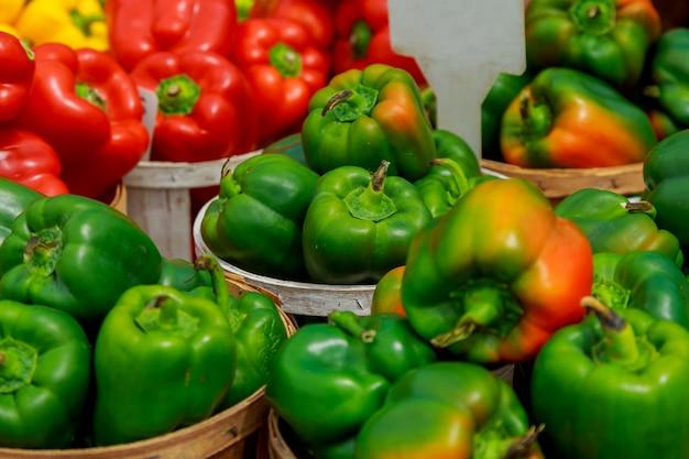 Świeży dojrzały czerwony słodki dzwonkowy pieprz w pudełku na sprzedaży przy sklepu spożywczego sklepem spożywczym. Premium Zdjęcia