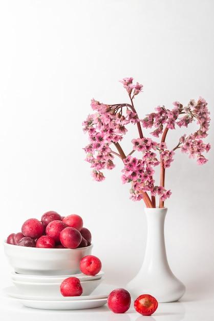 Świeży Minimalny Martwa Natura Ze śliwkowymi Wiśniami I Różowymi Fioletowymi Kwiatami Na Stole W Odcieniach Białego światła Premium Zdjęcia