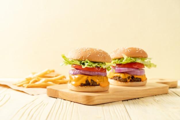 Świeży smaczny burger wołowy z serem i frytkami Premium Zdjęcia