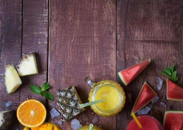 Świeży Wieloowocowy Smoothie W Szkle Z Owoc Na Brown Drewnianym Nieociosanym Tle, Mieszkanie Nieatutowy Premium Zdjęcia