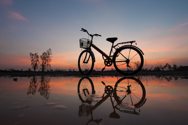 Sylwetka Bicykl Przy Zmierzchem I Odbiciem Premium Zdjęcia