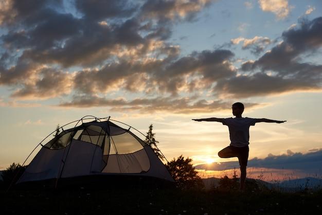Sylwetka Chłopca W Praktyce Jogi Na Szczycie Góry O świcie W Pobliżu Kempingu Pod Niebem Z Chmurami I Jasne Poranne Słońce. Zapierający Dech W Piersiach Krajobraz Gór I Wzgórz, Nad Którymi Wschodzi Słońce Premium Zdjęcia