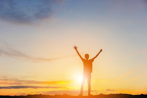 Sylwetka człowieka celebracja sukces szczęścia na szczycie góry wieczorne niebo zachód tło. Premium Zdjęcia