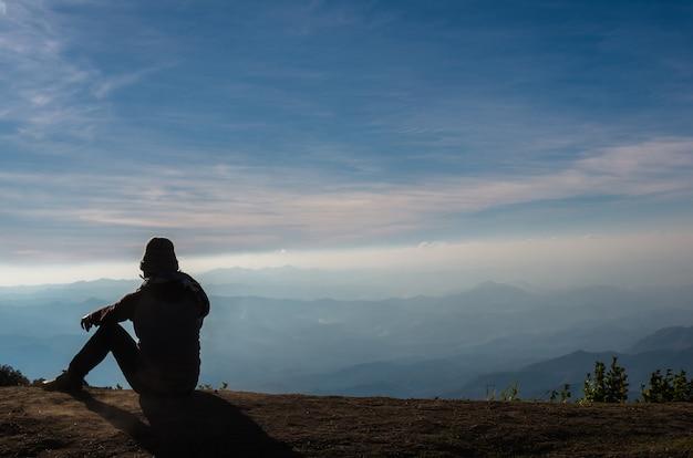 Sylwetka Człowieka, Który Siedzi I Patrząc Na Tle Krajobraz Gór Premium Zdjęcia