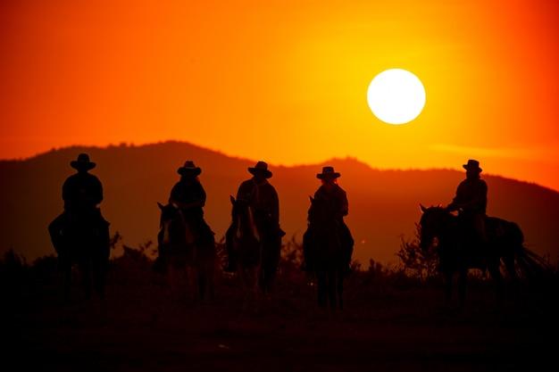 Sylwetka Człowieka Na Koniach Przed Zachodem Słońca Nad Górą Premium Zdjęcia
