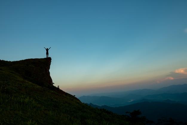 Sylwetka Człowieka Na Szczycie Góry Nad Niebo I Słońce Jasne Tło Premium Zdjęcia