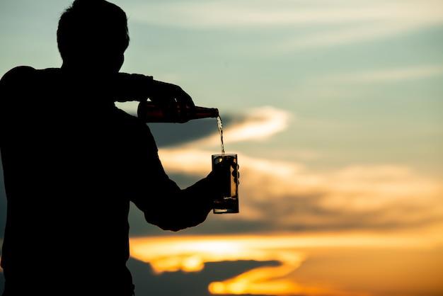 Sylwetka Człowieka Trzyma Piwo Podczas Zachodu Słońca Darmowe Zdjęcia
