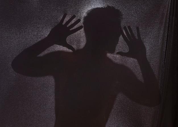 Sylwetka Człowieka Za Ciemne Tkaniny Premium Zdjęcia