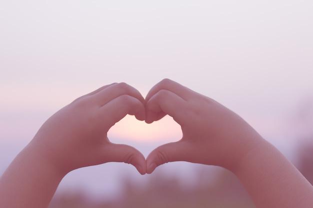 Sylwetka Dłoni Dzieci W Piękny Wschód Słońca Przechwytuje Słońce W Sercu. Premium Zdjęcia