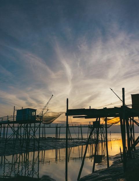 Sylwetka Drewniane Stojaki W Pobliżu Morza Podczas Zachodu Słońca Darmowe Zdjęcia