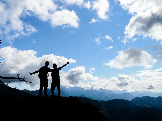 Sylwetka Dwóch Przyjaciół Razem Na Szczycie Góry Z Pięknym Krajobrazem Premium Zdjęcia