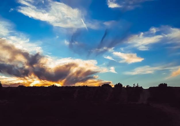 Sylwetka Dwóch Rowerzystów W Dół Wzgórza Podczas Pięknego Zachodu Słońca. Premium Zdjęcia