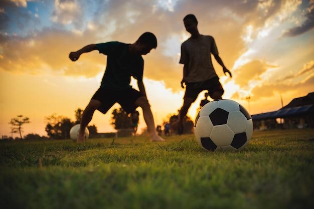 Sylwetka działania sport outdoors grupa dzieciaki ma zabawę bawić się piłka nożna futbol dla ćwiczenia. Premium Zdjęcia