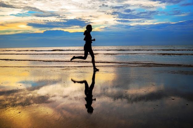 Sylwetka Kobiety Jogger Bieg Na Zmierzch Plaży, Sprawności Fizycznej I Zdrowego życia Pojęciu ,. Premium Zdjęcia