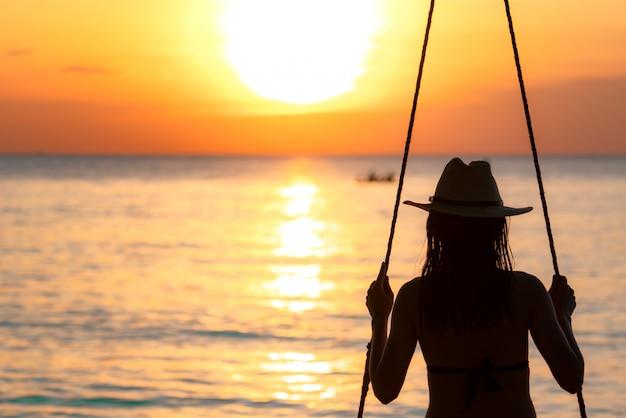 Sylwetka Kobiety Nosić Bikini I Słomkowy Kapelusz Huśtawka Huśtawki Na Plaży Na Letnie Wakacje O Zachodzie Słońca Premium Zdjęcia