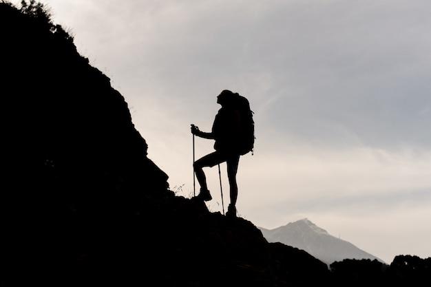 Sylwetka Kobiety Stojącej Na Skałach Z Plecakiem I Laski Premium Zdjęcia