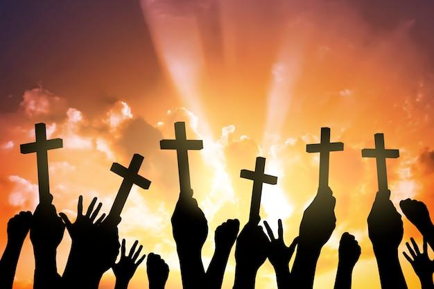 Sylwetka ludzi posiadających christian cross Premium Zdjęcia