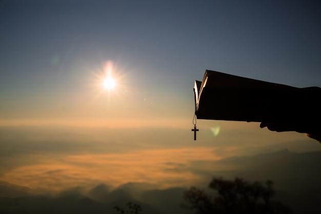 Sylwetka ludzka ręka trzyma biblię i krzyż, tło jest wschodem słońca Darmowe Zdjęcia
