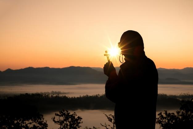Sylwetka ludzka ręka trzyma krzyż tło jest wschodem słońca Darmowe Zdjęcia