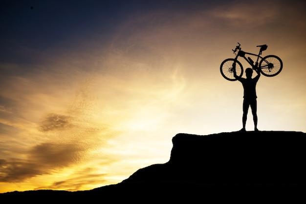 Sylwetka ludzki mienie rower górski Premium Zdjęcia