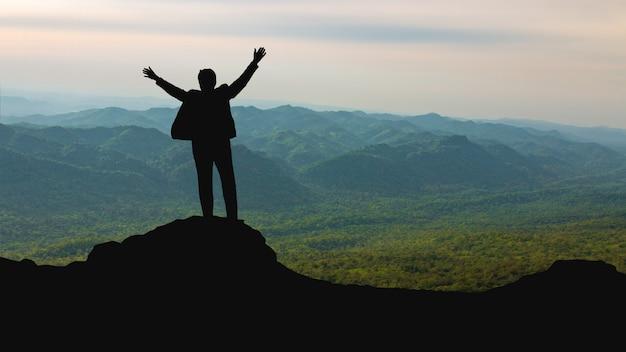 Sylwetka mężczyzna na góra wierzchołku nad nieba, słońca lekkim sukcesem, przywódctwo i ludzie pojęć Premium Zdjęcia
