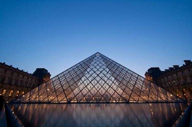 Sylwetka piramidy w luwrze w wieczór podczas wystawy antyki lata Premium Zdjęcia