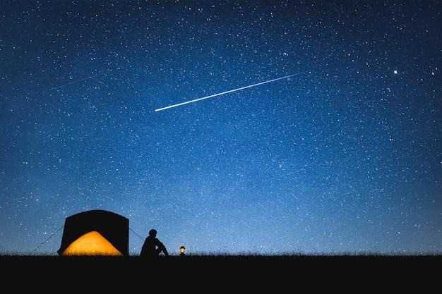 Sylwetka podróżnika camping na górskim i nocnym niebie z gwiazdami. tło. Premium Zdjęcia